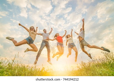 The five friends jumping on the grass on the sunny background