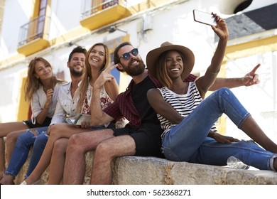 Five friends sitting on a wall in Ibiza taking a selfie