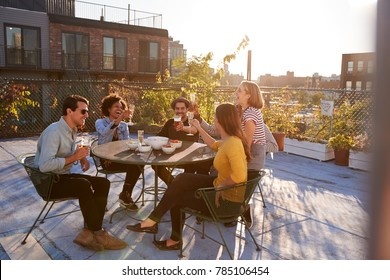 Five friends sitting at a table on a rooftop making a toast