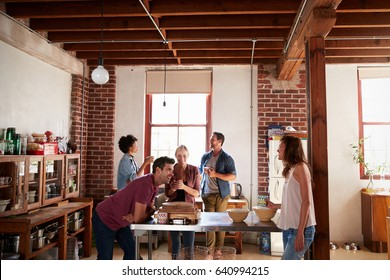 Five friends stand talking over coffee in a kitchen