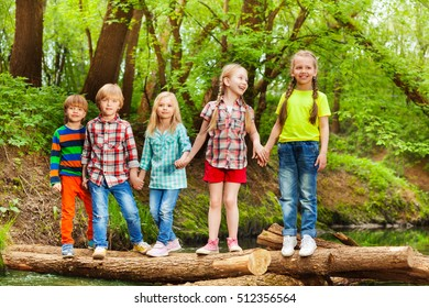 Five friends standing holding hands on log bridge