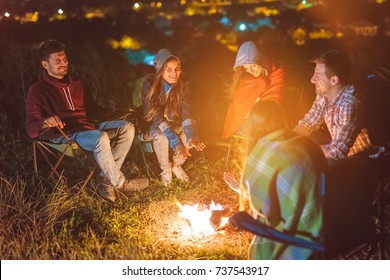 The five friends warming hands above the bonfire. evening night time