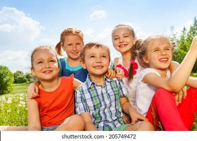 Five funny kids on a meadow