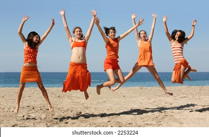 Five girls in orange clothes jumping on the beach