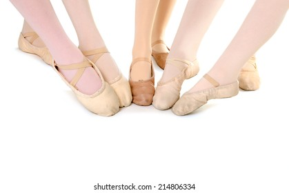 Five Girls point their ballet slippers together in the middle of class.