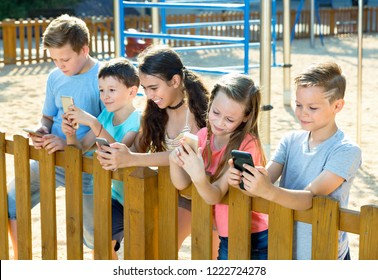 Five glad  cheerful positive smiling children sitting and playing in smartphone at the playground