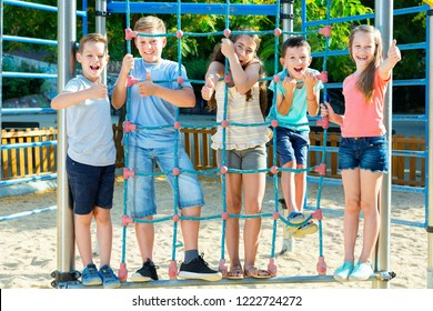 Five  glad kids posing  at the playground together
