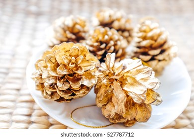 five golden pine cones on a hand-woven table.