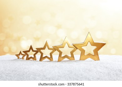 Five golden stars on snow in front of bright yellow light, christmas background, copy space