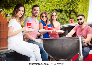 Five good looking young friends having a barbecue and eating burgers on a pick up truck next to a grill