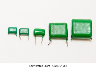 Five green film capacitors. Different siize capacitors. On white background