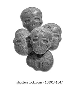 Five grey or gray army Skull, Ecstasy, MDMA, Amphetamine or medication pills shaped like a skull isolated on a white background.