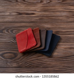 Five handmade leather cardholders on wooden background lie one on another. Stock photo with blurred background.