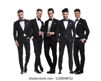 five handsome men in black tuxedoes standing together on white background, full body picture
