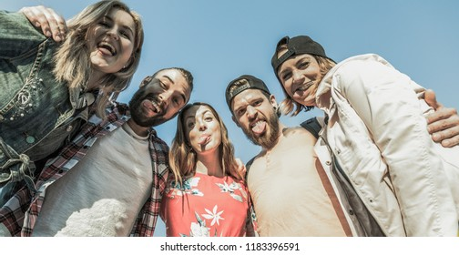 five happy best friends hanging out outdoor next to blue sky make silly faces sticking out their tongues looking down into the camera
