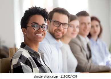 Five happy confident successful multiracial team smiling sitting together in office boardroom. Company is headed by a black leader boss woman focus on her face. Unity, coworkers team building concept