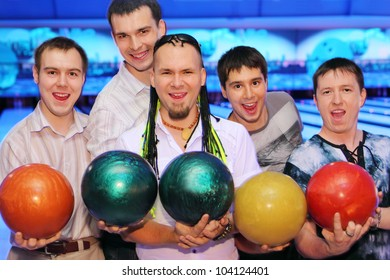 Five happy men hold balls in bowling club; friends relax together