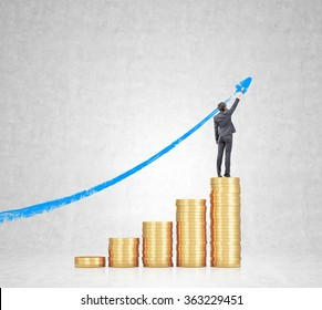 Five heaps of golden coins arranged as a bar chart, a businesswoman standing on the highest and painting a blue graph at the concrete background. Concept of career growth.