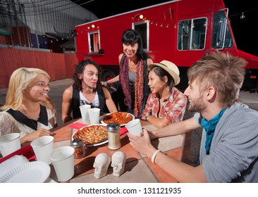 Five hipsters at mobile pizza restaurant with plates of food