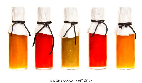 Five hot sauce bottles with white tops on a white background
