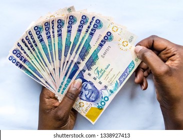 Five hundred Naira notes spread out in hand isolated on white background. Nigerian Naira. African woman's hand holding five hundred Naira Nigerian for payment concept