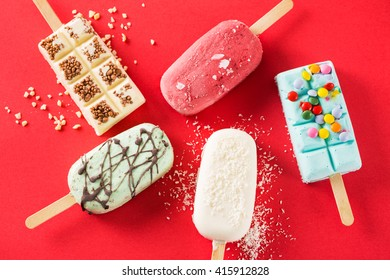 Five ice creams with different tastes on red background.From above