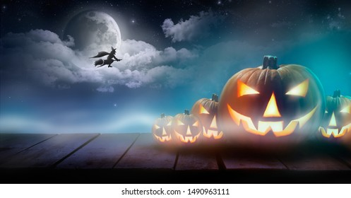 Five Jack O Lanterns on a rustic wooden bench with a witch on broomstick flying past a large moon and glowing clouds.