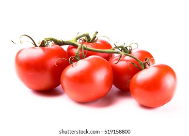 Five juicy red shiny tomatoes on a green vine laying on a white background