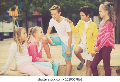 Five kids are communicating about football on walk in the park.