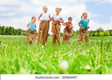 Five kids having fun jumping in sacks on a dandelion meadow