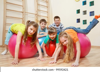 Five kids playing with gymnastic balls