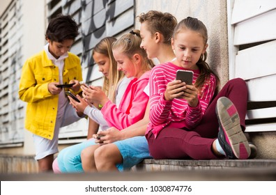 Five kids are playing on phone in the playground.