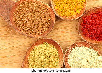 Five kind of Spices in Wooden Spoons (on wooden chopping board).