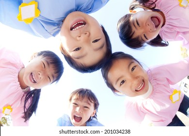 Five kindergarten children laughing in a circle