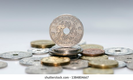 Five kroner coin standing on a pile of other Danish coins with selective focus. The krone is the official currency of Denmark, Greenland, and the Faroe Islands, introduced on 1 January 1875.