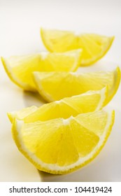 Five lemon wedges on a white plate. This is not an isolation.