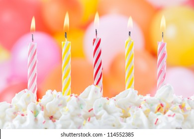 Five lit birthday candles on colorful balloons background