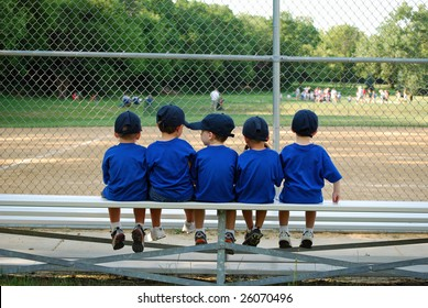 five little boys sit on a bench and wait for their baseball / t-ball game to begin