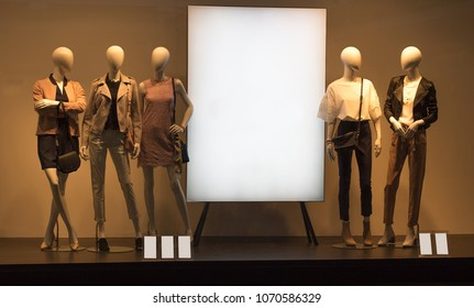 Five mannequins standing in store window display of women's casual clothing near the stand