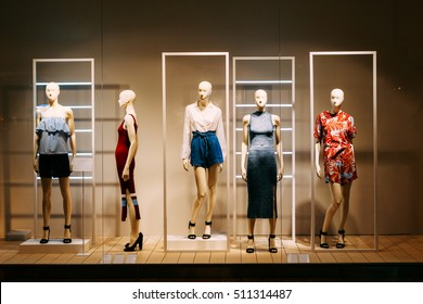 Five Mannequins Standing In Store Window Display Of Women's Casual Clothing Shop In Shopping Mall.