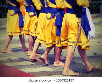 Five men of Sikh Religion with long dresses walking barefoot through the streets of the city with toned old effect