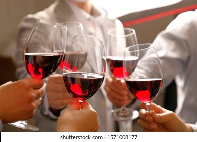 Five men and women toasting red wine