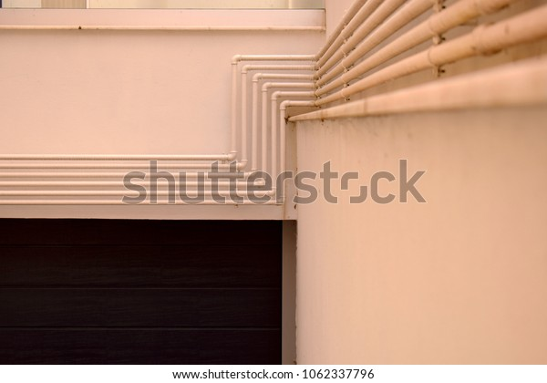 five metal pipes placed in line on a wall
