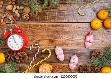 Five minutes before the new year. Cozy wooden background Christmas sweets and toys pigs. View from above. Place under your text.