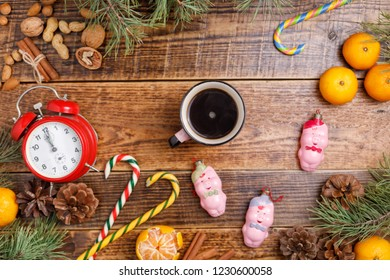 Five minutes before the New Year and a cup of coffee. Cozy wooden background Christmas sweets and toys pigs. Place under your text.