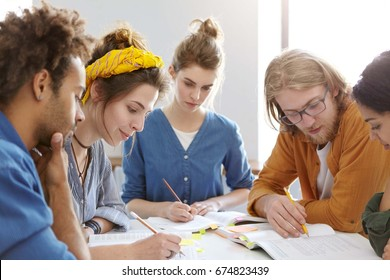 Five mixed race college students sitting together at table underline important information in books for their project having serious expressions helping each other. People and cooperation concept