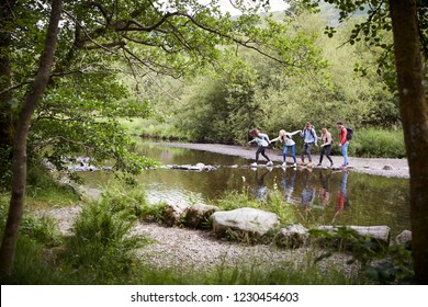 Five mixed race young adult friends during a hike start stepping on stones to cross a stream while holding hands to help each other