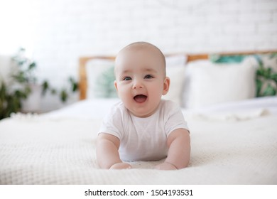 Five months baby boy. Adorable baby boy in sunny bedroom. Newborn child relaxing in bed. Nursery for children