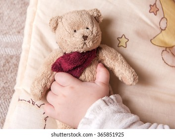 five months old  sweet baby sleeping on a blanket with a bear