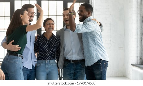 Five multi ethnic students or company employees accomplish project, exam pass, embracing feels excited celebrating common success giving high 5, gesture of unity racial equality and friendship concept
